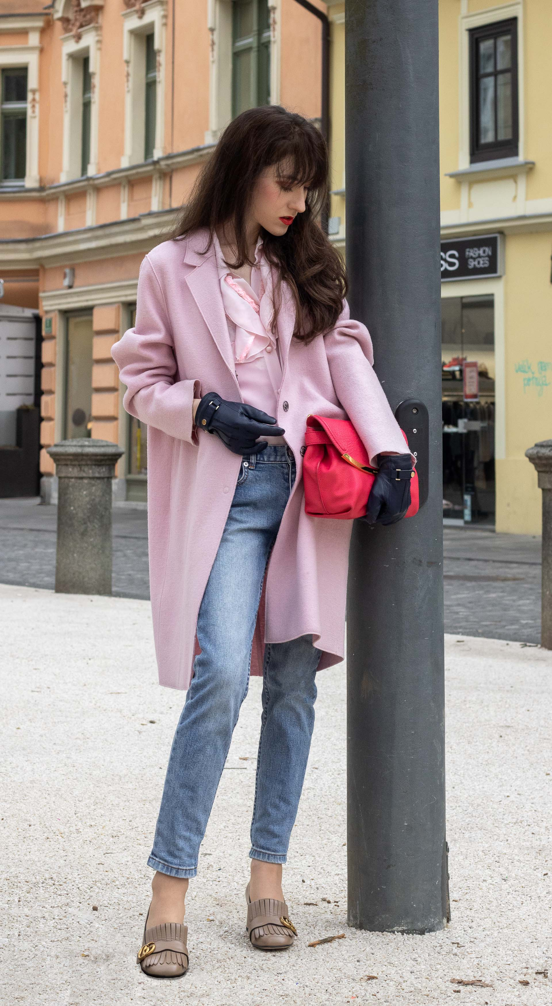 Fashion blogger Veronika Lipar of Brunette from Wall Street wearing A.P.C. blue jeans Harris Wharf London pink coat Red Valentino pink blouse pink pouch bag leather gloves Gucci heeled loafers on the street in-between seasons