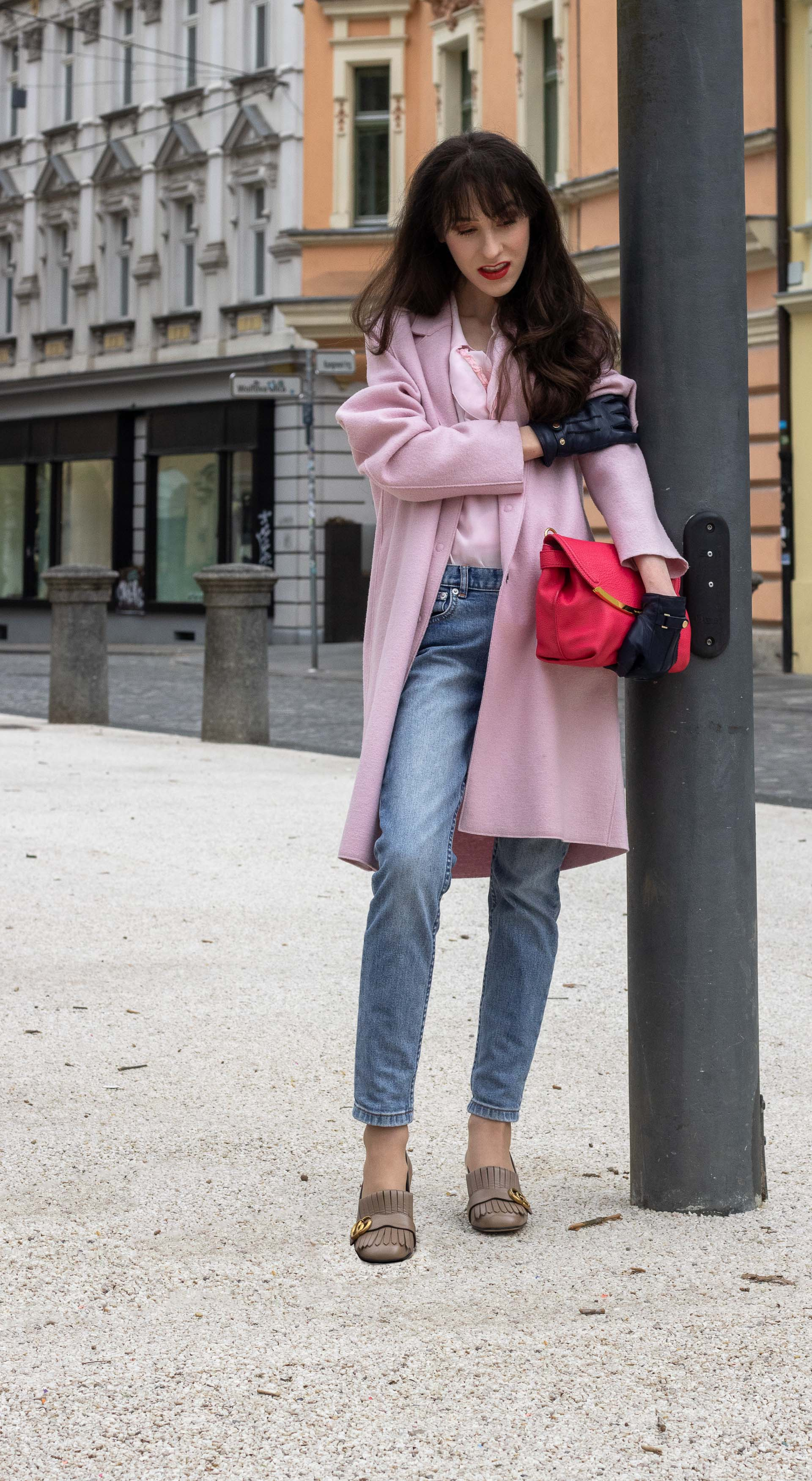 Fashion blogger Veronika Lipar of Brunette from Wall Street dressed in A.P.C. blue jeans Harris Wharf London pink coat Red Valentino pink blouse pink pouch bag leather gloves Gucci heeled loafers on the street in-between seasons
