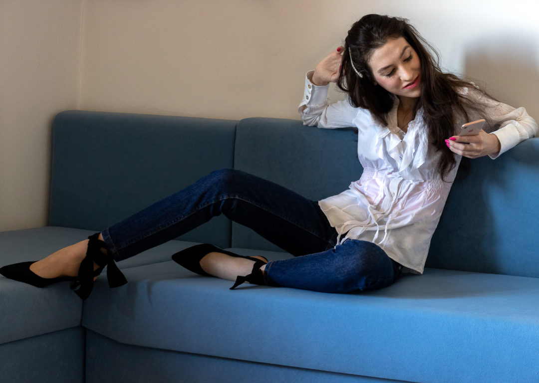 Fashion blogger Veronika Lipar of Brunette from Wall Street wearing ruffled white blouse dark blue A.P.C. Paris jeans Ganni black Sabine pumps pearl hair pin sitting on the couch