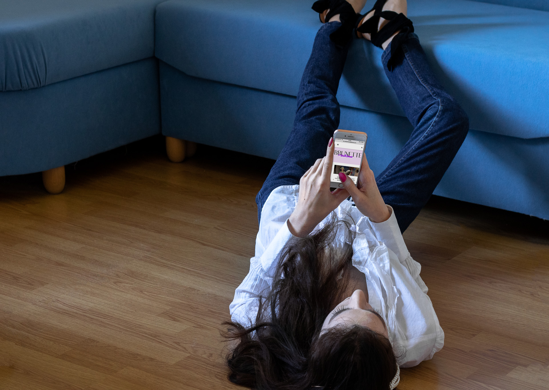 Fashion blogger Veronika Lipar of Brunette from Wall Street wearing ruffled white blouse dark blue A.P.C. Paris jeans Ganni black Sabine pumps pearl hair pin lying on the couch