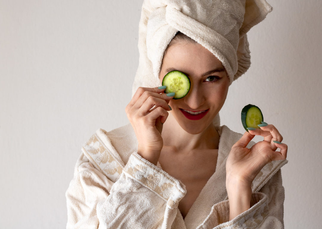 Fashion blogger Veronika Lipar of Brunette from Wall Street wearing bathrobe having hair wrapped in towel holding cucumbers