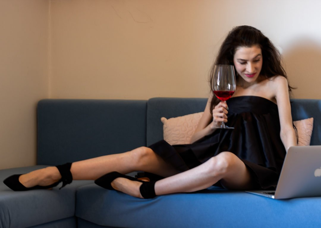 Fashion blogger Veronika Lipar of Brunette from Wall Street wearing Rotate Birger Christensen voluminous little black dress Ganni black pumps for zoom party sitting on the couch