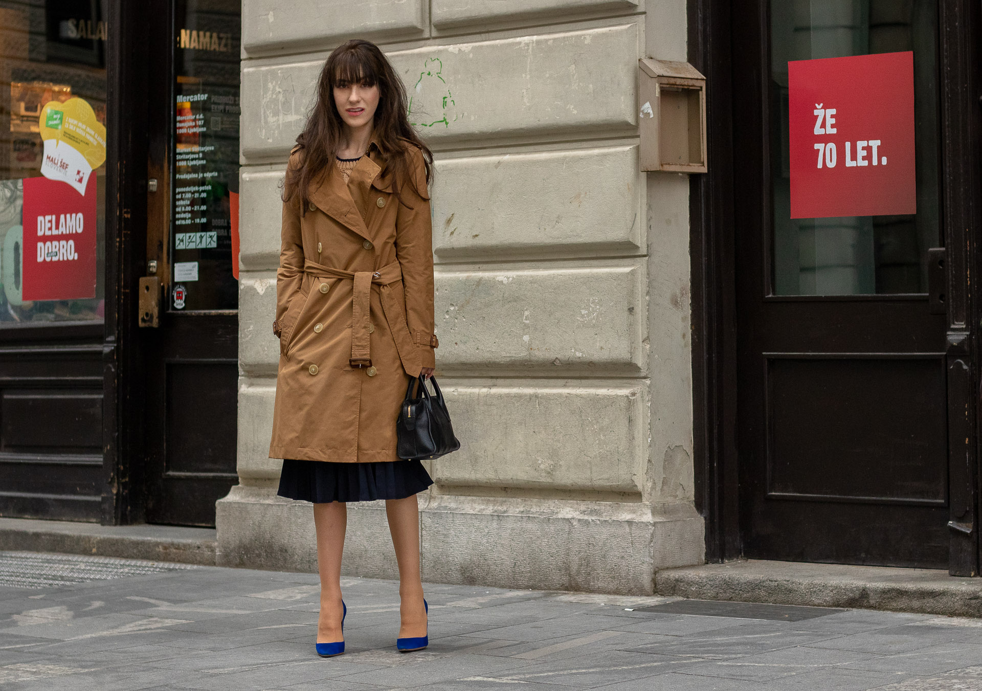 Beautiful Fashion blogger Veronika Lipar of Brunette from Wall Street wearing camel Burberry trench coat and blue pleated midi skirt with Gianvito Rossi blue pumps on the street in spring