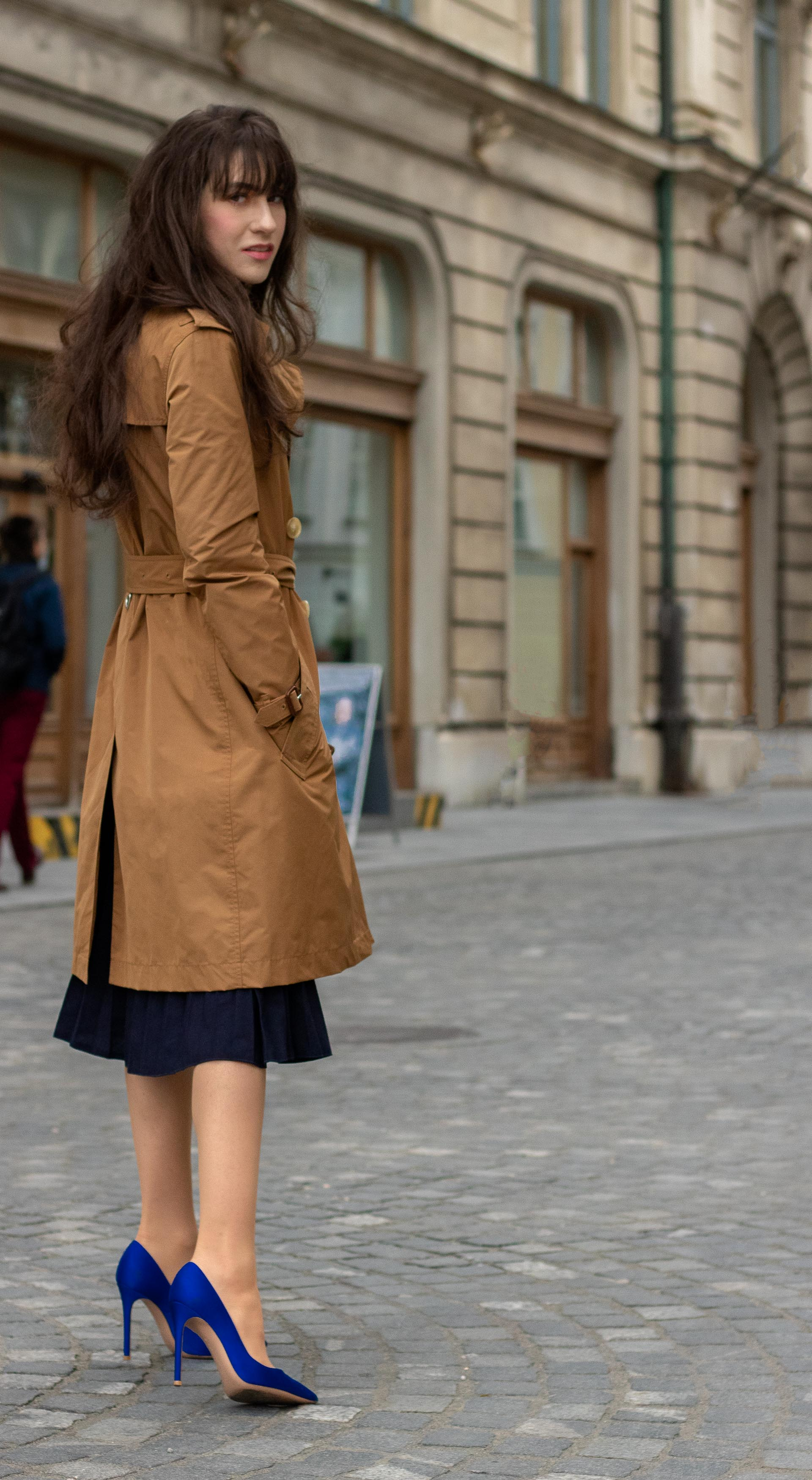 Beautiful Fashion blogger Veronika Lipar of Brunette from Wall Street wearing camel Burberry Kensington trench coat and blue pleated midi skirt with Gianvito Rossi blue pumps on the street in spring