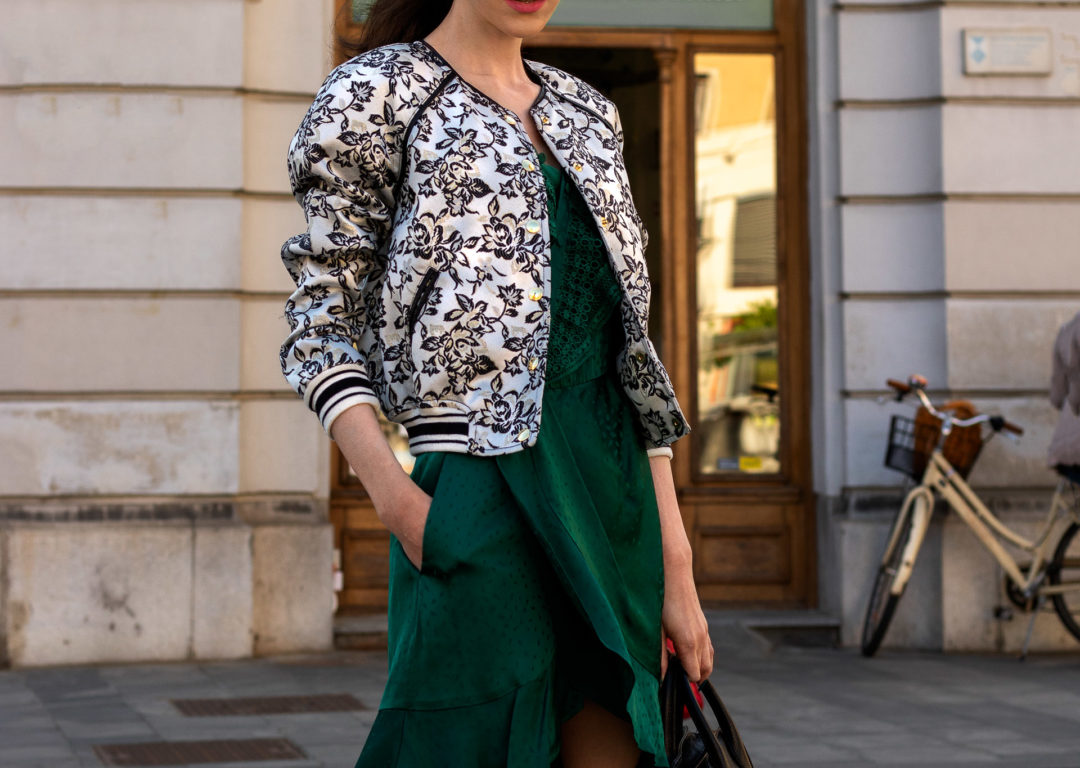 Fashion blogger Veronika Lipar of Brunette from Wall Street wearing Self-Portrait emerald green wrap dress and bomber jacket for a date