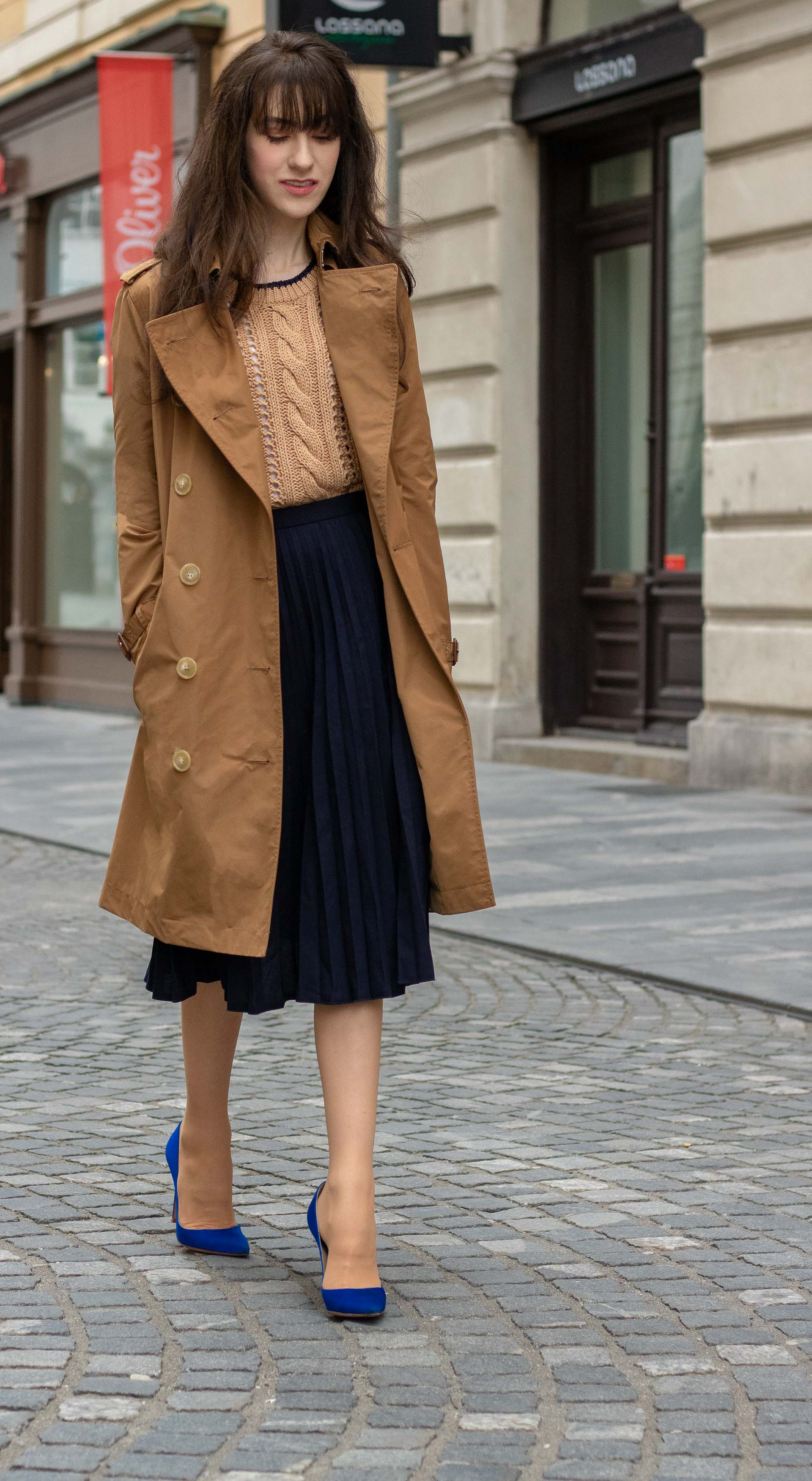 Beautiful Fashion blogger Veronika Lipar of Brunette from Wall Street dressed in camel Mando sweater camel Burberry Kensington trench coat and blue pleated midi skirt with Gianvito Rossi blue pumps on the street in spring