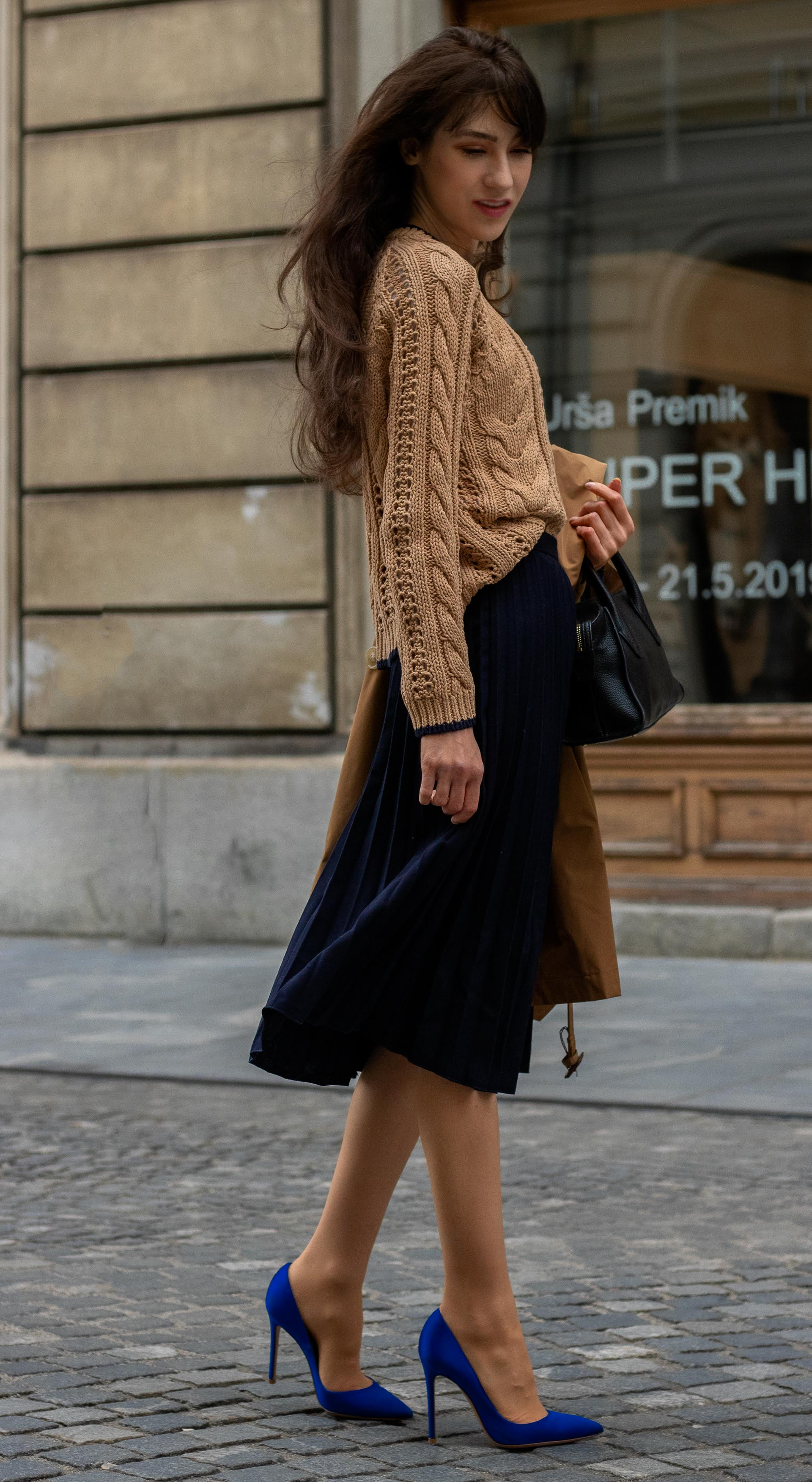 Fashion blogger Veronika Lipar of Brunette from Wall Street wearing camel Mango knit sweater and blue pleated midi skirt with Gianvito Rossi blue pumps on the street in spring