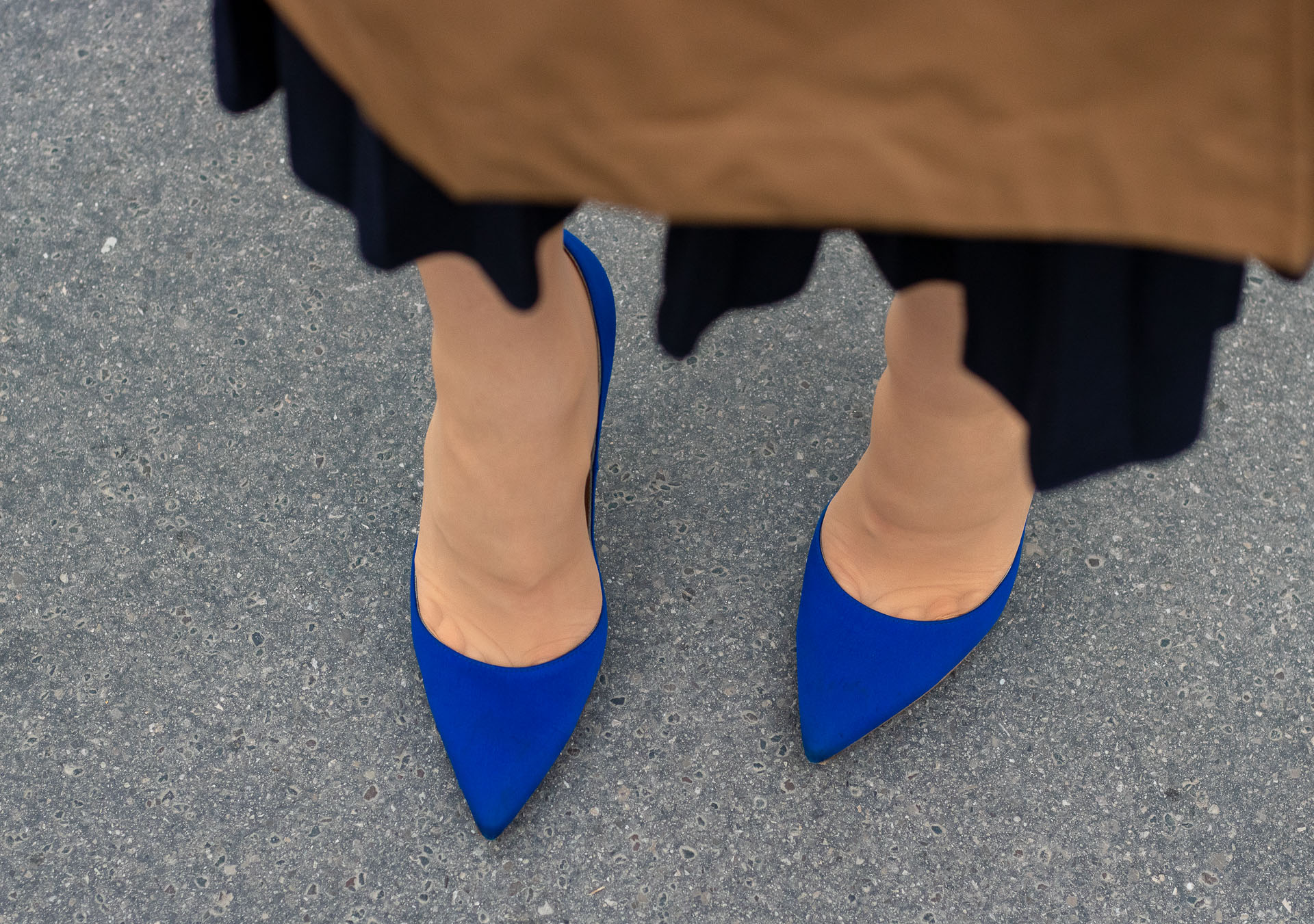 Fashion blogger Veronika Lipar of Brunette from Wall Street wearing Burberry trench coat over blue pleated midi skirt with Gianvito Rossi blue pumps on the street in spring