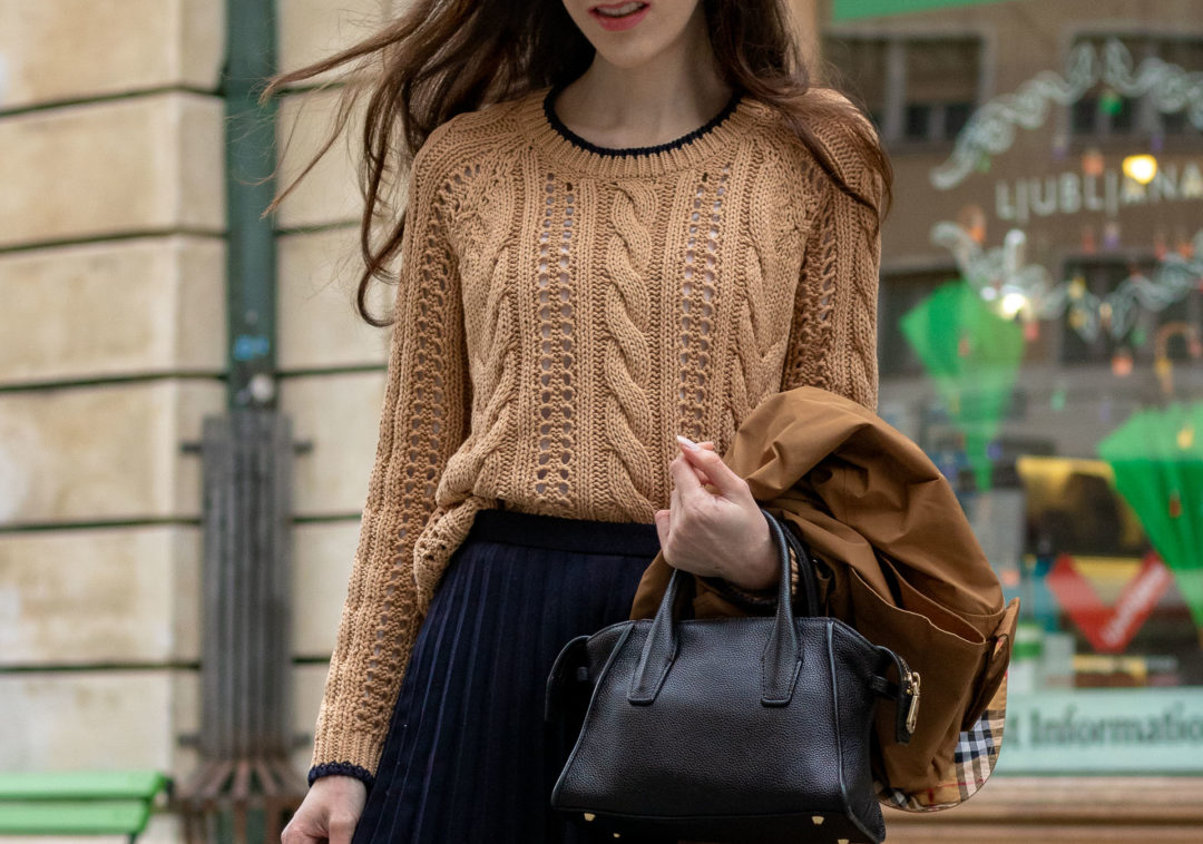 Must follow fashion blogger Veronika Lipar of Brunette from Wall Street wearing Mango cable knit camel sweater blue pleated midi skirt black top handle holding camel beige Burberry Kensington trench coat in her hand standing on the street