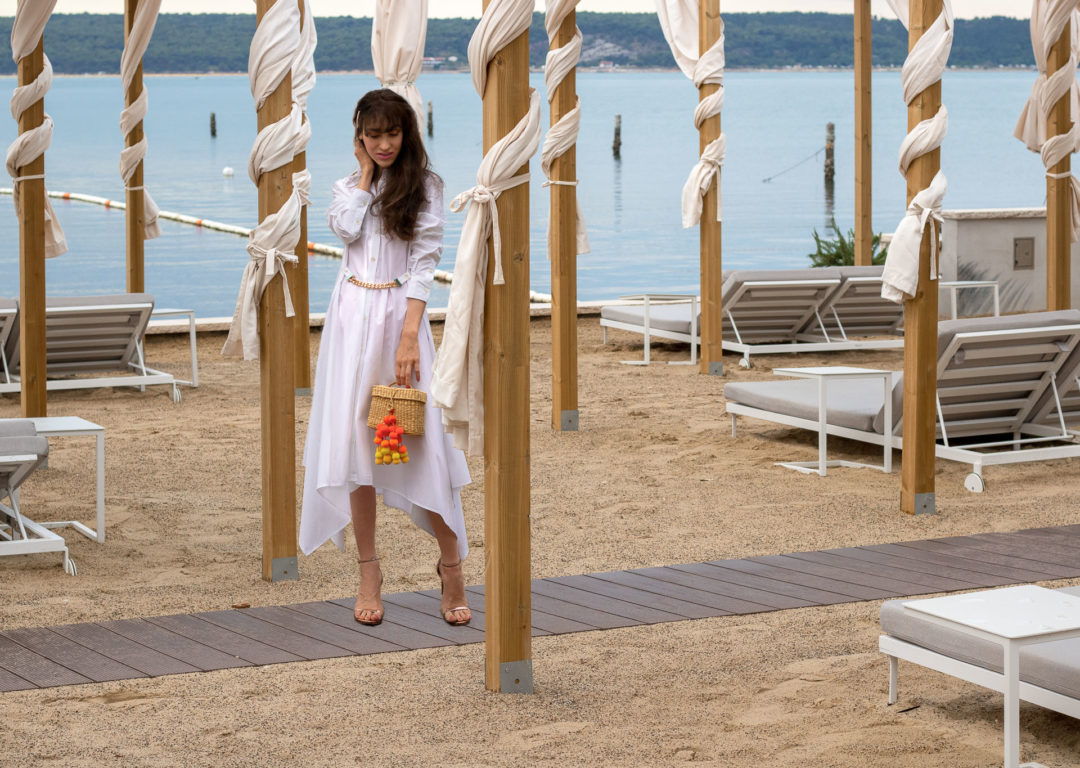 Fashion blogger Veronika Lipar of Brunette from Wall Street wearing JW Anderson shirtdress with chain belt Nannacay basket bag Stuart Weitzman Nudistsong sandals on the beach