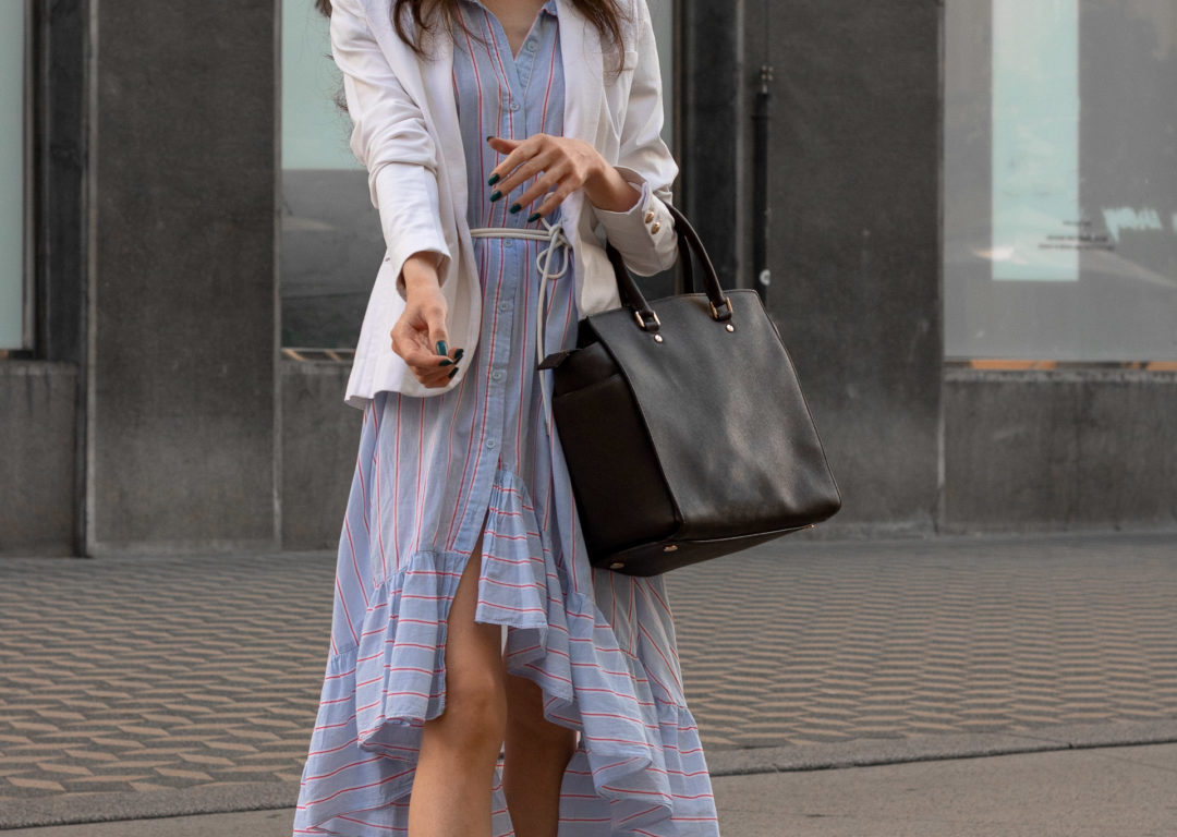 Fashion blogger Veronika Lipar of Brunette from Wall Street wearing white blazer over shirt dress with business bag for work in summer