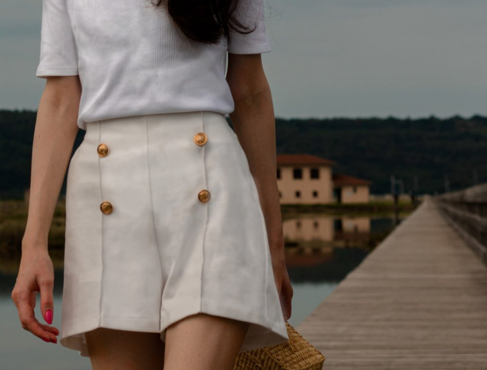 Fashion blogger Veronika Lipar of Brunette from Wall Street wearing white summer shorts white ribbed top Nannacay basket bag